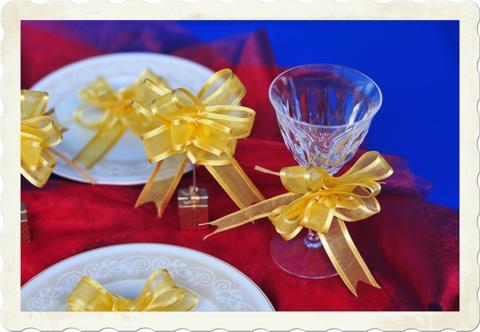 Festliche Tischdekoration zu Silvester mit goldenen Organza Zierschleifen
